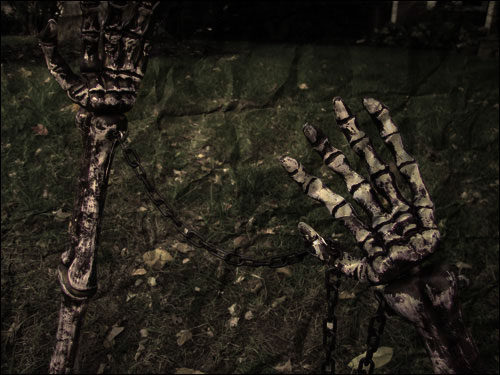 Skeleton hands reaching up from someone's lawn